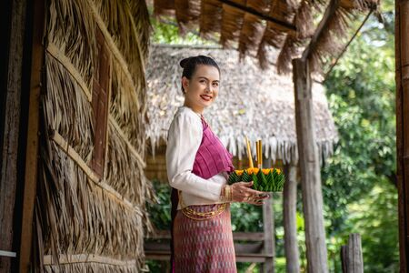 Beautiful woman ware Traditional Thai dresses hold floating basket or kratong, loy kratong festival in Thailand 스톡 콘텐츠