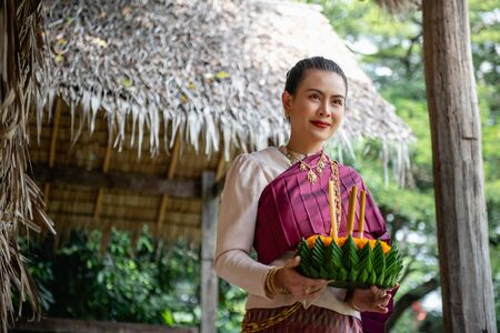 Beautiful woman ware Traditional Thai dresses hold floating basket or kratong, loy kratong festival in Thailand 스톡 콘텐츠 - 133214199