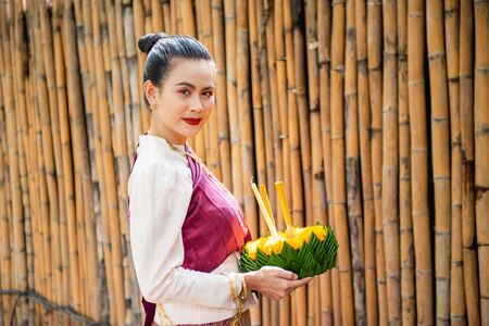 Beautiful woman ware Traditional Thai dresses hold floating basket or kratong, loy kratong festival in Thailand 스톡 콘텐츠 - 133214283