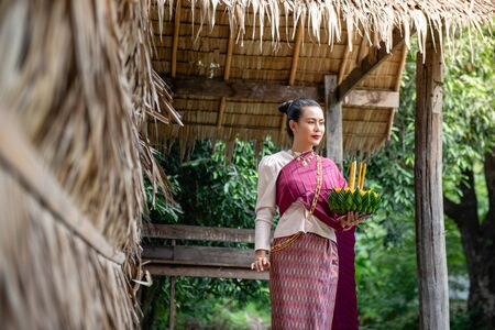 Beautiful woman ware Traditional Thai dresses hold floating basket or kratong, loy kratong festival in Thailand 스톡 콘텐츠 - 133214204