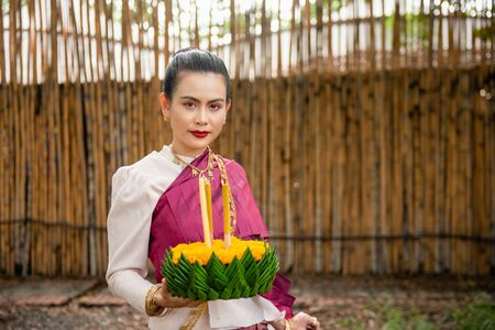 Beautiful woman ware Traditional Thai dresses hold floating basket or kratong, loy kratong festival in Thailand 스톡 콘텐츠 - 133214206