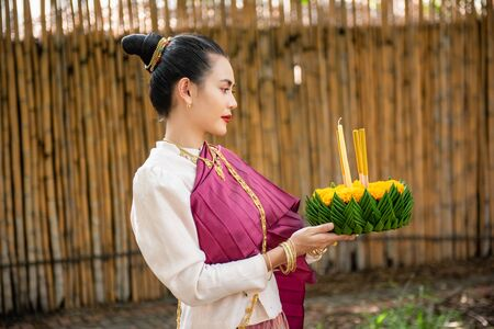 Beautiful woman ware Traditional Thai dresses hold floating basket or kratong, loy kratong festival in Thailand 스톡 콘텐츠 - 133214057