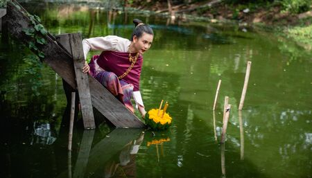 Beautiful woman ware Traditional Thai dresses hold floating basket or kratong, loy kratong festival in Thailand 스톡 콘텐츠 - 133214058