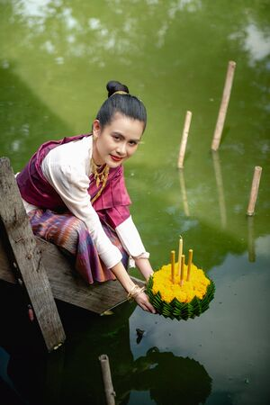 Beautiful woman ware Traditional Thai dresses hold floating basket or kratong, loy kratong festival in Thailand 스톡 콘텐츠 - 133214059