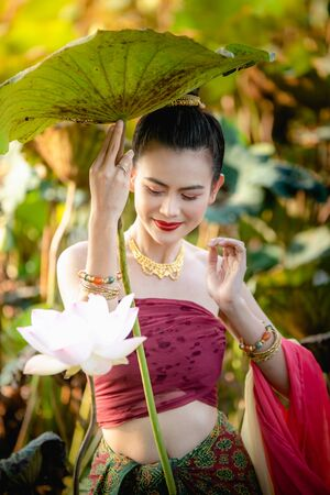 Asian woman collecting lotus flowers and she wear Traditional Thai dresses, Thailand