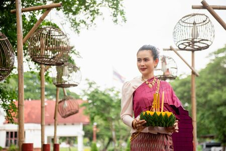 Beautiful woman ware Traditional Thai dresses hold floating basket or kratong, loy kratong festival in Thailand 스톡 콘텐츠 - 133214080