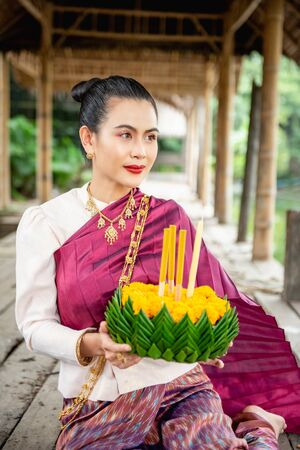 Beautiful woman ware Traditional Thai dresses hold floating basket or kratong, loy kratong festival in Thailand 스톡 콘텐츠 - 133214089