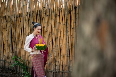 Beautiful woman ware Traditional Thai dresses hold floating basket or kratong, loy kratong festival in Thailand 스톡 콘텐츠 - 133214096
