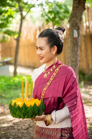 Beautiful woman ware Traditional Thai dresses hold floating basket or kratong, loy kratong festival in Thailand 스톡 콘텐츠 - 133214102