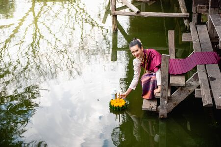 Beautiful woman ware Traditional Thai dresses hold floating basket or kratong, loy kratong festival in Thailand 스톡 콘텐츠 - 133214106