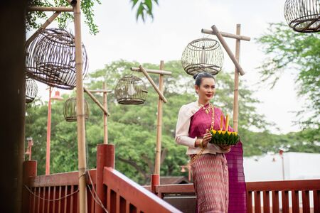Beautiful woman ware Traditional Thai dresses hold floating basket or kratong, loy kratong festival in Thailand 스톡 콘텐츠 - 133214110
