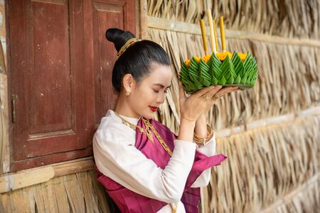Beautiful woman ware Traditional Thai dresses hold floating basket or kratong, loy kratong festival in Thailand 스톡 콘텐츠 - 133214116