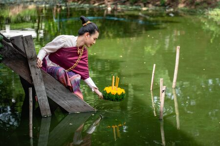 Beautiful woman ware Traditional Thai dresses hold floating basket or krathong, loy krathong festival in Thailand 스톡 콘텐츠 - 133213779