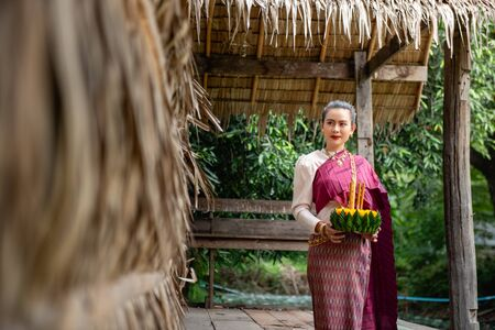 Beautiful woman ware Traditional Thai dresses hold floating basket or krathong, loy krathong festival in Thailand 스톡 콘텐츠 - 133213802