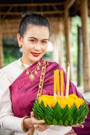 Beautiful woman ware Traditional Thai dresses hold floating basket or krathong, loy krathong festival in Thailand 스톡 콘텐츠 - 133213813