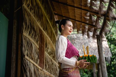 Beautiful woman ware Traditional Thai dresses hold floating basket or krathong, loy krathong festival in Thailand 스톡 콘텐츠 - 133213819