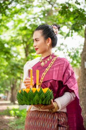 Beautiful woman ware Traditional Thai dresses hold floating basket or krathong, loy krathong festival in Thailand 스톡 콘텐츠 - 133213864