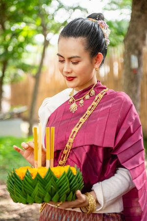 Beautiful woman ware Traditional Thai dresses hold floating basket or krathong, loy krathong festival in Thailand 스톡 콘텐츠 - 133213919