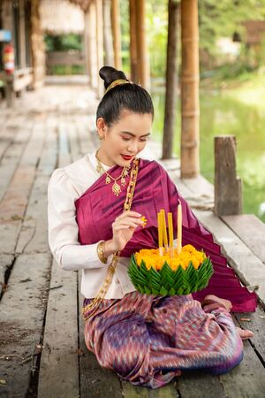 Beautiful woman ware Traditional Thai dresses hold floating basket or krathong, loy krathong festival in Thailand 스톡 콘텐츠 - 133214009
