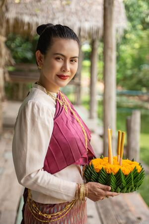 Beautiful woman ware Traditional Thai dresses hold floating basket or krathong, loy krathong festival in Thailand 스톡 콘텐츠 - 133213345