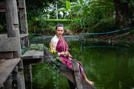 Beautiful woman ware Traditional Thai dresses hold floating basket or krathong, loy krathong festival in Thailand 스톡 콘텐츠 - 133213354