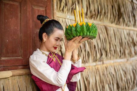 Beautiful woman ware Traditional Thai dresses hold floating basket or krathong, loy krathong festival in Thailand
