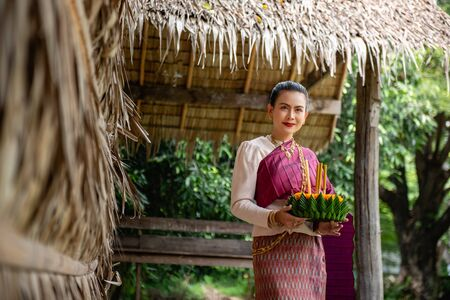 Beautiful woman ware Traditional Thai dresses hold floating basket or krathong, loy krathong festival in Thailand 스톡 콘텐츠 - 133213494