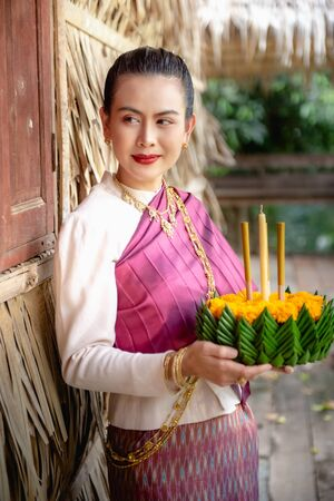Beautiful woman ware Traditional Thai dresses hold floating basket or krathong, loy krathong festival in Thailand 스톡 콘텐츠 - 133213519