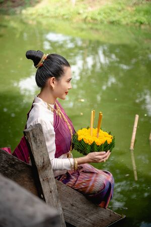 Beautiful woman ware Traditional Thai dresses hold floating basket or krathong, loy krathong festival in Thailand 스톡 콘텐츠 - 133213559