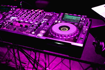 Dj hands on equipment deck and mixer with turntable dj in the nightclub at party Editorial