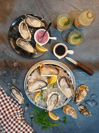 Fresh Opened Oysters on ice in dish with lemon and lime
