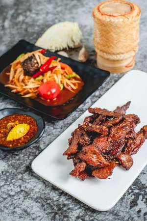 deep fried sun-dried pork (Moo dad deaw) with papaya salad(som tum), Thai food