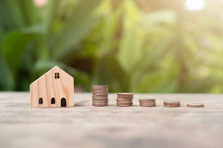 Money Coins arranged in graph neatly stack and there is a small wooden house, Green bokeh and flare light, Concept saving money, growth, economic, business and investment.