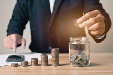 Businessman carrying a coin takes it in a glass jar with a pile of coins on the side and is using a smartphone. Concept investment , finance, businessman, planning, saving money, accounting.