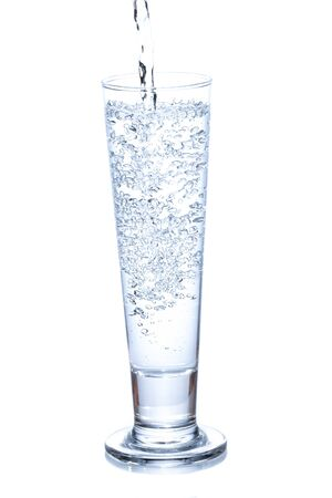 water pouring in a glass on white background  photo