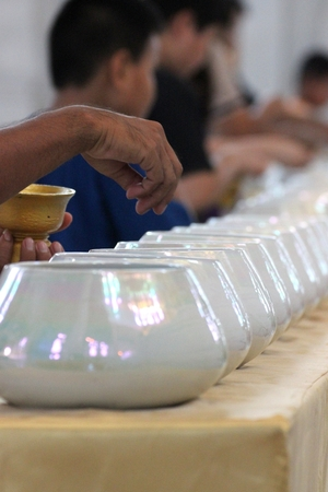 tradition thai donation, throwing coin into monk alms bowl