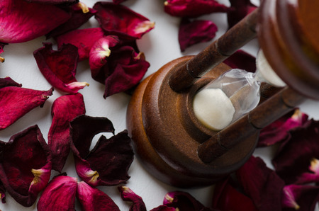 Dried rose petal with sandglass. Time is runing out. Stock Photo