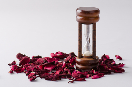 sear: Dried rose petal with sandglass. Time is runing out. Stock Photo