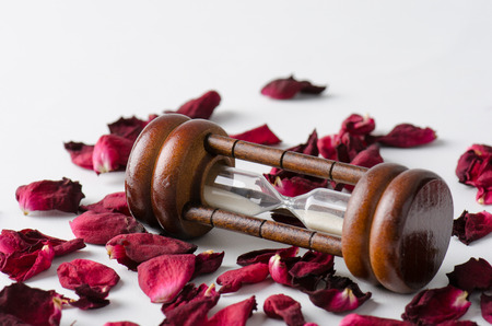 runing: Dried rose petal with sandglass. Time is runing out. Stock Photo
