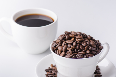 afternoon break: Coffee bean in the cup with black coffee close up shot