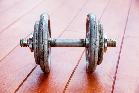 Iron dumbbell on a wooden deck.