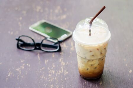 iced coffee: Iced coffee, smartphone and glasses on the wood table. Stock Photo