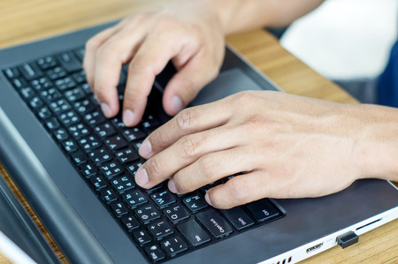 Man typing on laptop keyboard. Stock Photo