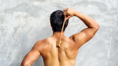 scratcher: Man scratching his back with a wooden backscratcher.