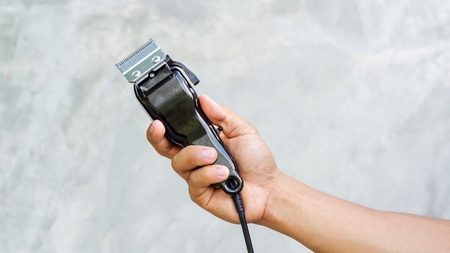 Man holding hair clipper in his hand. Stock Photo