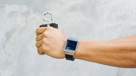 Man wear a smartwatch and use handgrips for exercise. Stock Photo