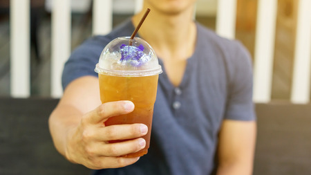 potation: Man drinking an iced fruit tea in a cafe.
