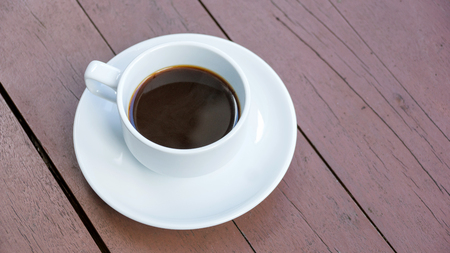 potation: Hot black coffee in a white cup on a wooden table. Stock Photo