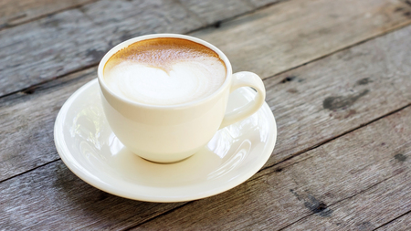 invigorate: Hot coffee in a white cup on a wooden table.