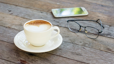 invigorate: Hot coffee, glasses, and smartphone on a wooden table.